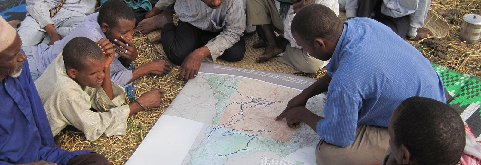 Researcher goes over maps with locals abroad